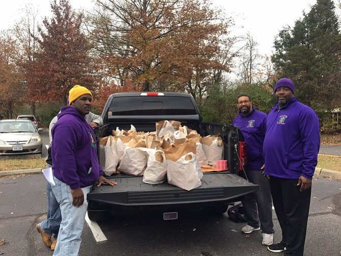 Members of the Sigma Mu Mu Chapter of Omega PSI Phi Fraternity, Incorporated, Reginald Parker, Marc Byer (hidden), Eric Martin, and Paul Forbes unload groceries for LINK's Thanksgiving Holiday Program.
