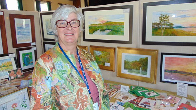 Linda Jones, president of Great Falls Studios, with her watercolors and mixed media paintings.