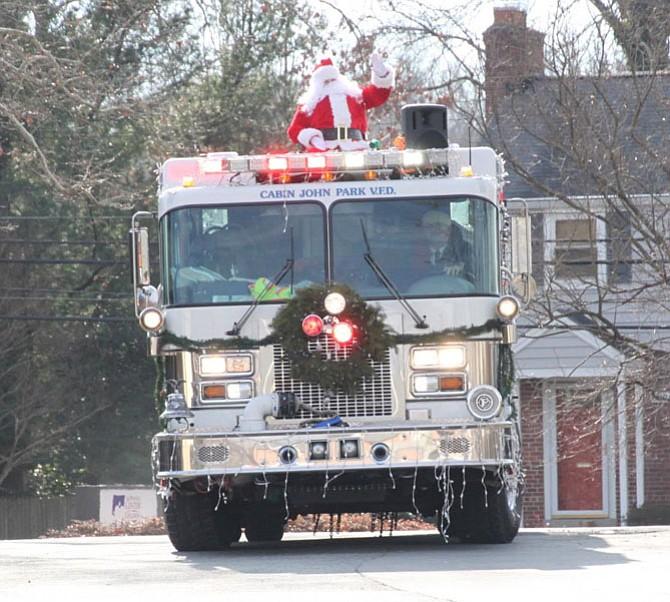 Santa waves from a Cabin John Park Volunteer Fire Department fire truck.