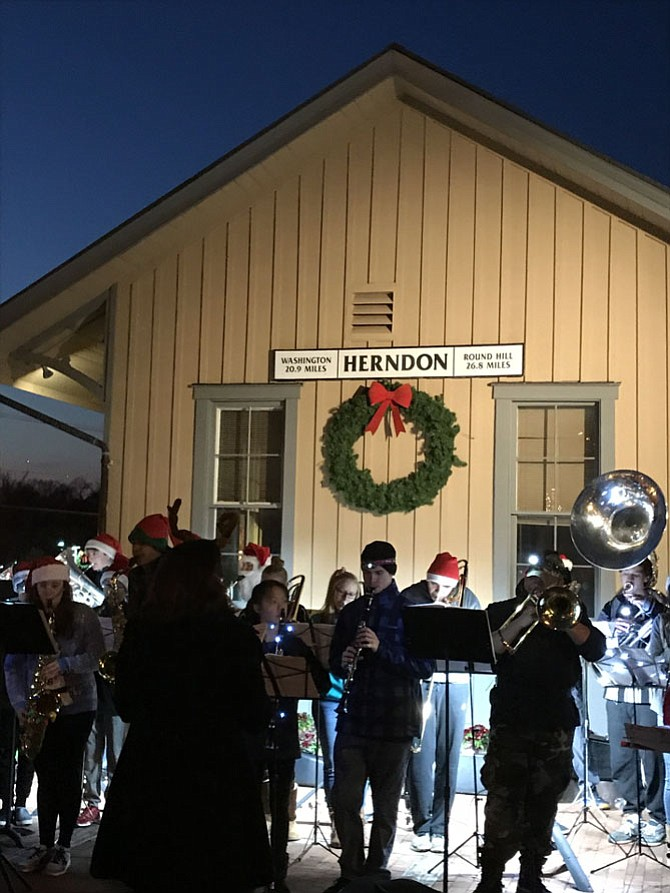 Members of the Herndon High School Band don Santa hats as they perform during the Town of Herndon's Hometown Holidays Tree Lighting and Sing-Along held Saturday evening, Dec. 2.