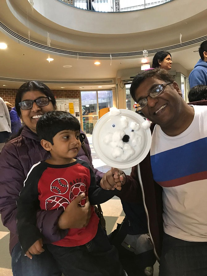 Saharsh Maram, 3, of Herndon shows off the paper plate polar bear puppet he made at the Winter Open House/Santa's Workshop. Saharsh's parents, Rajttha Maram and Srinadh Maram, give Saharsh's hand a big polar bear love hug.