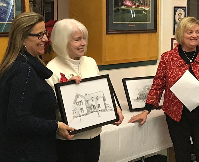 Patti Kelly, owner of 106 Monroe Hill Court accepts the pen and ink drawing of her home created by local artist Pat Macintyre during the reception held for the five homeowners whose properties were featured on The 2017 Holiday Homes Tour of Herndon. Homes Tour committee Co-chair, Susan Anselene looks on.
