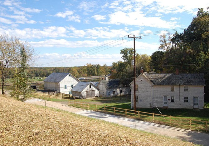 "The Woodlawn barn complex in its current configuration. At right is the historic Otis Mason House, which the Federal Highway Administration moved from its nearby original site. At the far left is the historic ""bank barn,"" so named because of its location on the sloping bank of the hill. That allows simple access to both the upper and lower levels. The smaller structure in the middle is the corn crib, with the dairy between it and the house. The new Route 1 bypass is in the background."