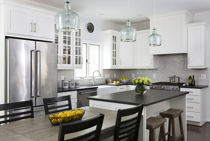 Black granite countertops and white cabinetry help modernize this Herndon kitchen by Winn Design + Build.