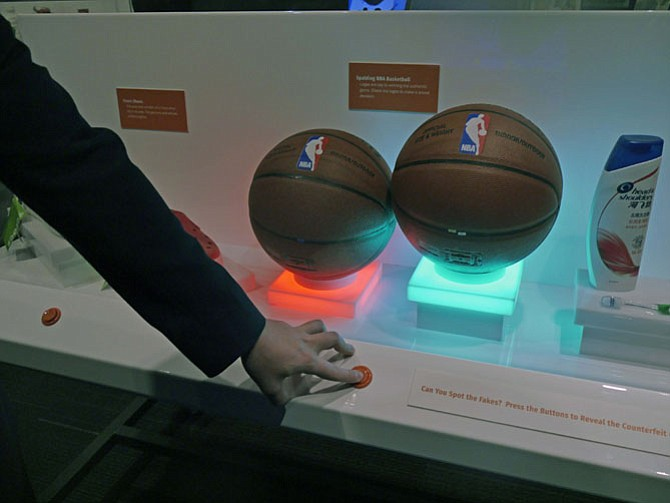 Brandon Allton stops at a display for visitors to identify the patented Spalding basketball from the nearly identical forgery.