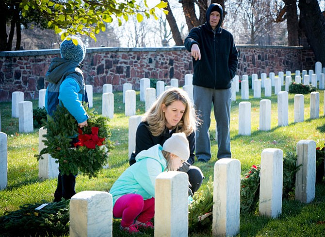 Volunteers place a wreath at a gravesite in Alexandria National Cemetery Dec. 16 as part of the nationwide Wreaths Across America event.