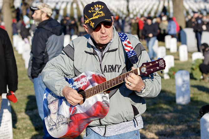 Craig Gross of Tarpon Springs, Fla., plays a song at his son's gravesite during the Dec. 16 Wreaths Across America event at Arlington National Cemetery. CPL Frank R. Gross was killed by an IED while on patrol in Afghanistan on July 16, 2011.