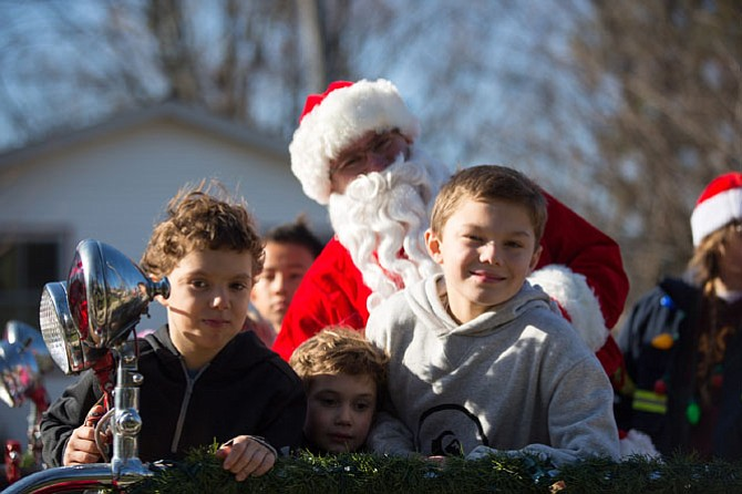 Santa, Elliot Zaret of Great Falls, pictured with Vienna neighborhood residents, (from left) Jacob Lucca, 7, Thomas Lucca, 5, and Logan Lucca, 9, on the classic fire truck for a Santa run Saturday, Dec. 16 in Vienna.
