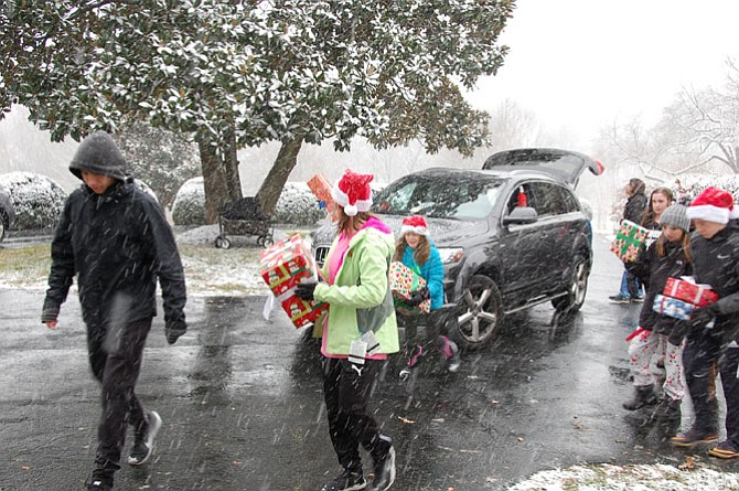 Snow falls as volunteers bring gifts to the Wish List Project drop-off Dec. 9.