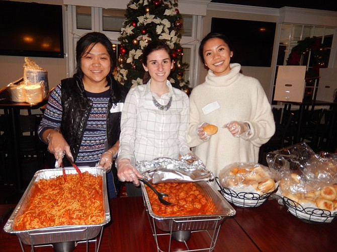 Serving up spaghetti, meatballs and rolls to the parents and children are (from left) FACETS volunteers Miranda Lan, Katie Plaster and Ngan Pham.