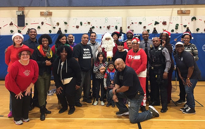 First responders from across the city gather for a photo Dec. 23 at Samuel Tucker Elementary School after distributing more than 800 toys to children and families in need.