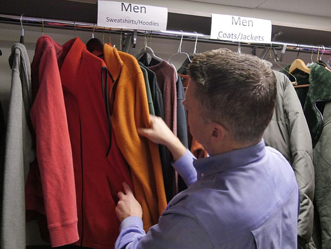 Scott Miller, senior development director for A-SPAN, sorts through the racks of sweatshirts and jackets in the clothing room at the center. He says Arlington Realtors Care (ARC) recently donated a lot of heavy jackets to the center.