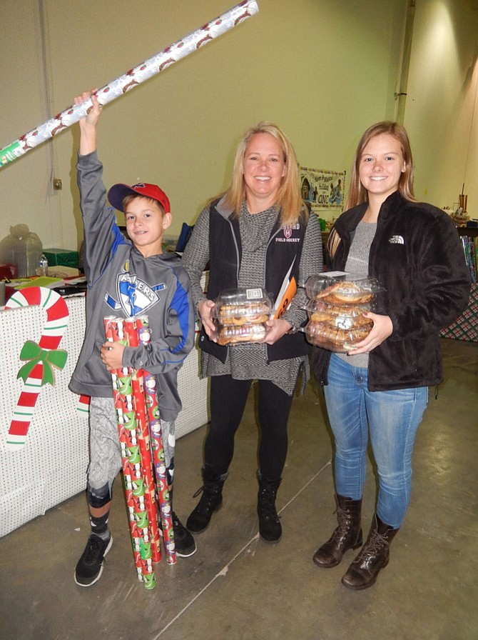 Carrying wrapping paper and cookies to be delivered with each family's gifts are (from left) Virginia Run Elementary fifth-grader Jay Rennyson, mom Lisa Rennyson and sister Callie, a Harvard University sophomore and 2016 Westfield grad.