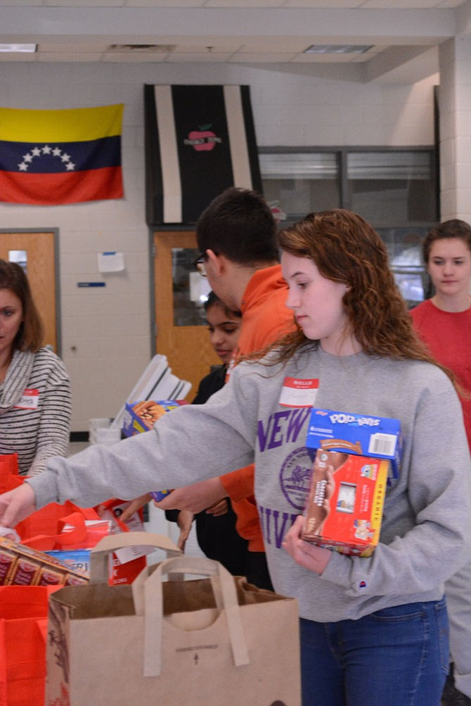 Herndon High senior Hannah Overton sorts food for delivery to area schools. Hannah is one of the many, reliable teen volunteers who have helped to make Food For Neighbors a success.