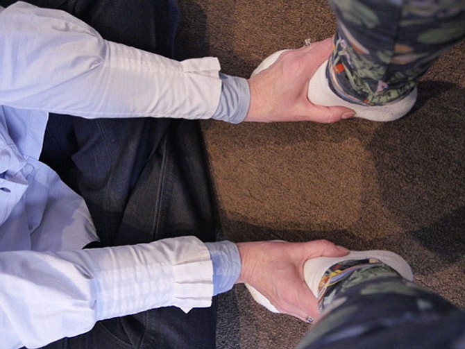 Mara Benner sits cross-legged in her office as she begins a meditation session by placing hands on a client's feet. This is one of many techniques to make people more mindful of the body-mind connection.