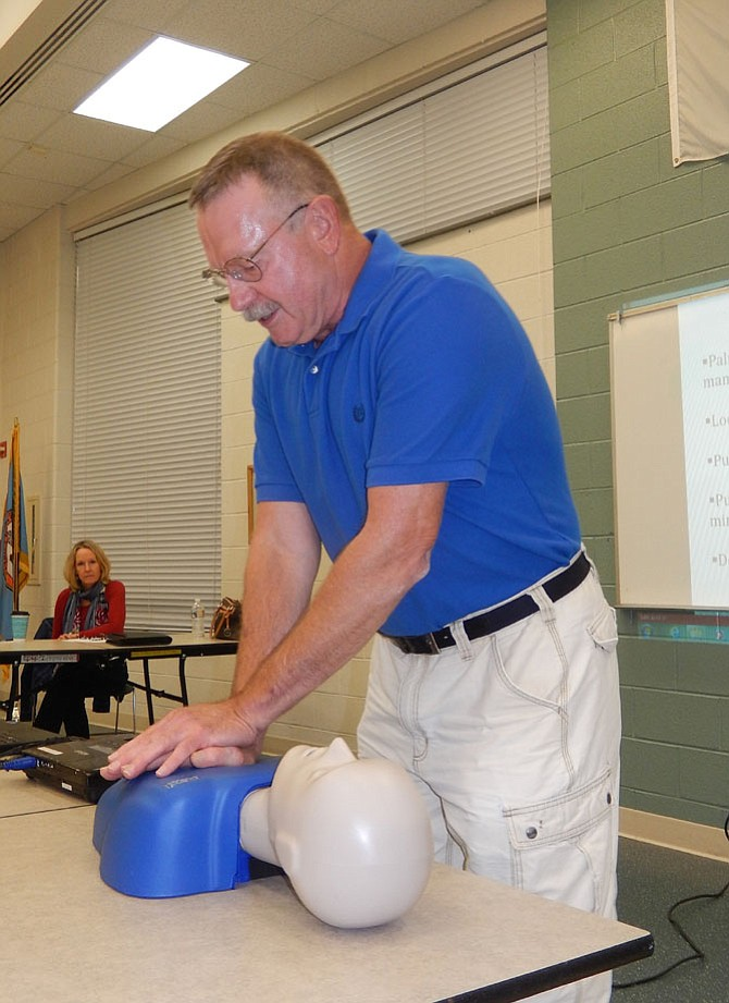Demonstrating CPR, EMT/paramedic Gary Orski locks his arms and uses his upper-body strength and abdominal muscles to compress this mannequin's chest.