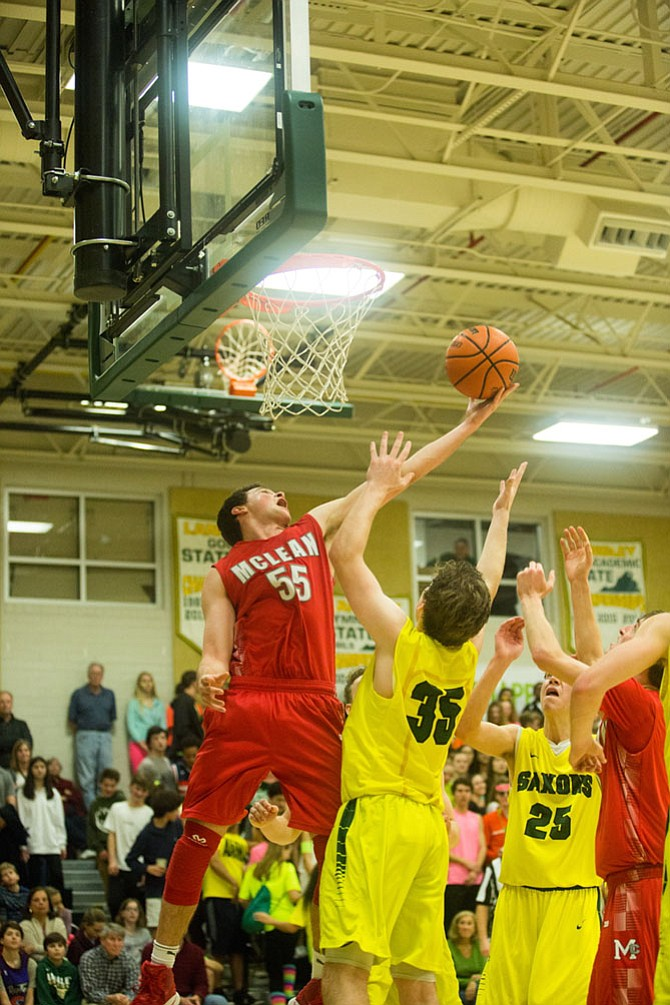 McLean Highlanders forward, Andrew Hale #55, junior, goes for a rebound against Langley Saxon defenders Friday night in a rivalry game at Langley High School.