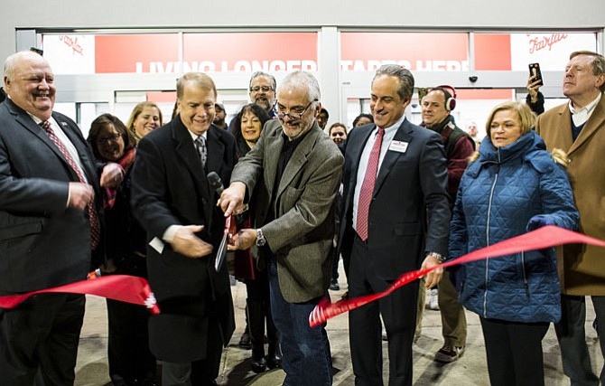 Mayor David Meyer (second from left) helps cut Earth Fare's ribbon, Jan. 10, with company officials, plus City Council members Ellie Schmidt, Jennifer Passey, Michael DeMarco and Janice Miller, and City Manager Bob Sisson (at far right).
