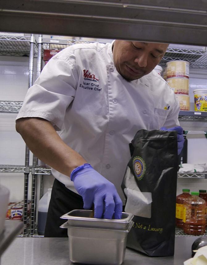 Chef Oscar Cruz picks a handful of golden raisins…