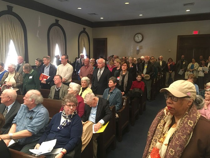 Advocates in favor of the Episcopal Church of the Resurrection's proposed West End affordable housing project stand in support at a City Council public hearing on Saturday, Jan. 20. Many wore Housing Alexandria and VOICE buttons, two coalitions representing an array of community organizations.
