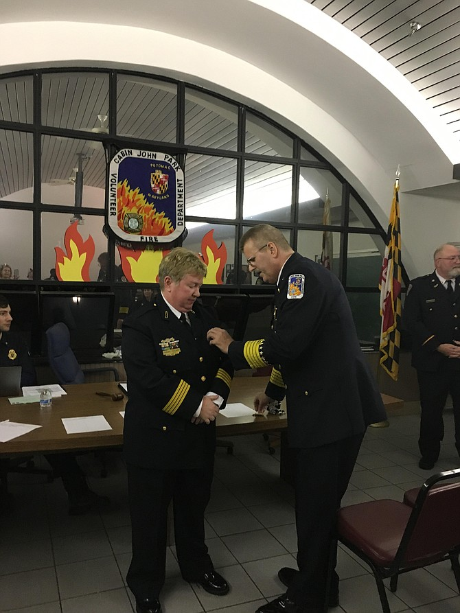 Retired Chief James Seavey pins the chief's badge on Corinne Piccardi, who was sworn in as new head of the Cabin John Park Volunteer Fire Department on Monday, Jan. 22.