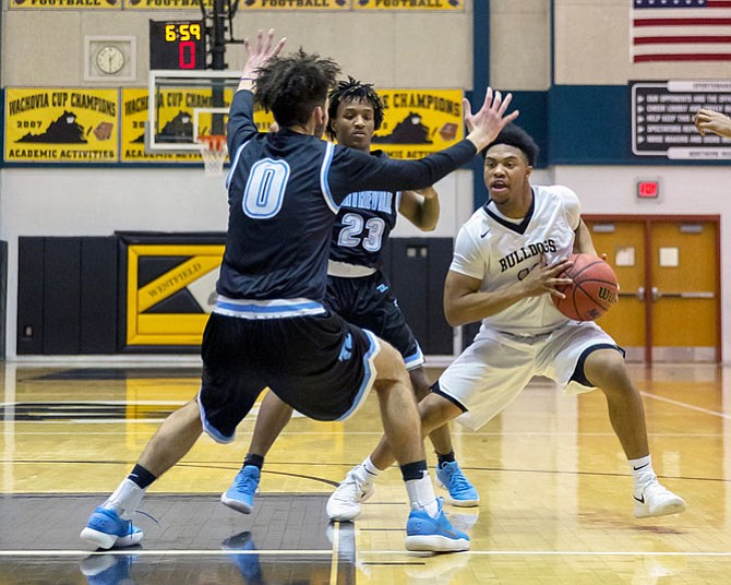 DJ Gregory #10 drives while being defended by #0 Ahmed Ghousheh and #23 Jordan Porter.