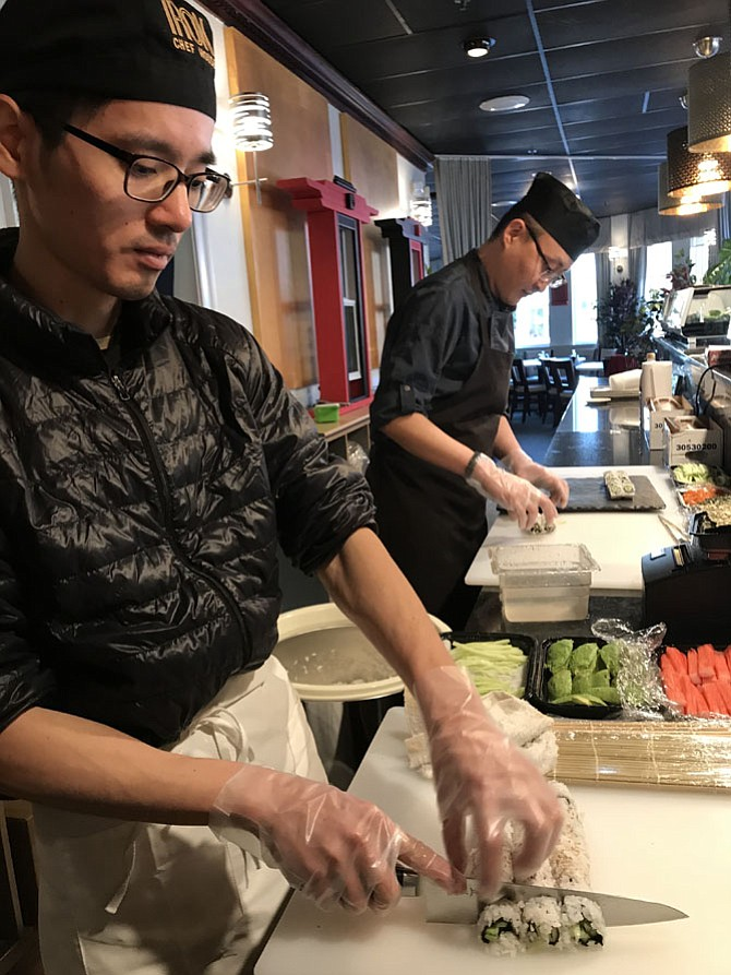 At the Grand Opening of Red Kimono Japanese & Korean Cuisines held Friday, Jan. 26, 2018, Sushi Chef, Zhen Chen of Vienna (front) slices rows of sushi while Head Sushi Chef, Dongsoo Kim of Centreville begins to prepare another set.