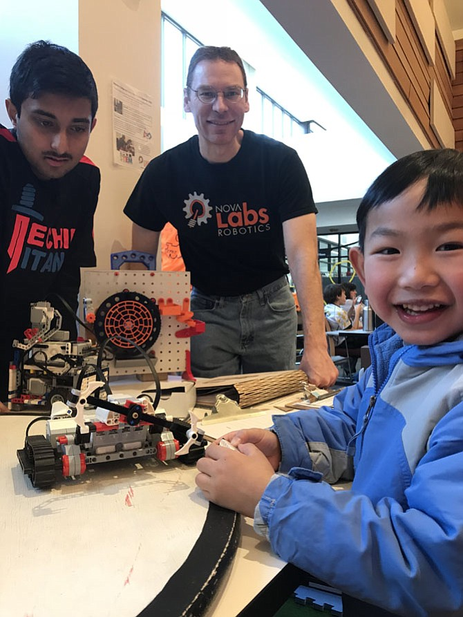 "During the Reston Camp Expo 2018 held at Reston Community Center on Saturday, Jan. 27, 2018, Ryan Le, 5, of Wolf Trap tries out a ""bot"" created by makers at NOVA Labs. From left: NOVA Labs makers Sathvik Narayana, 14 of Centreville and Spencer Allain look on."