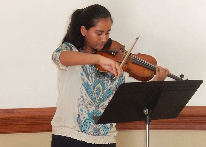 Mahika Ghaisas, with the American Youth Philharmonic Orchestra, plays the violin during the library's anniversary event.