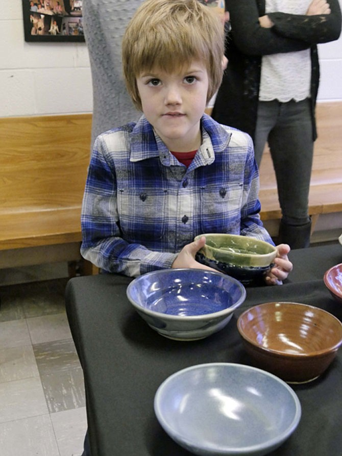 Colin Smith walks around the table studying each bowl and finally chooses a green one.