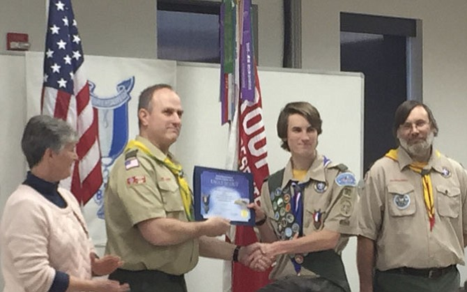 Michael Cohen, shaking the hand of Scoutmaster Kent Pankratz, is flanked by parents, Dawn and Don.