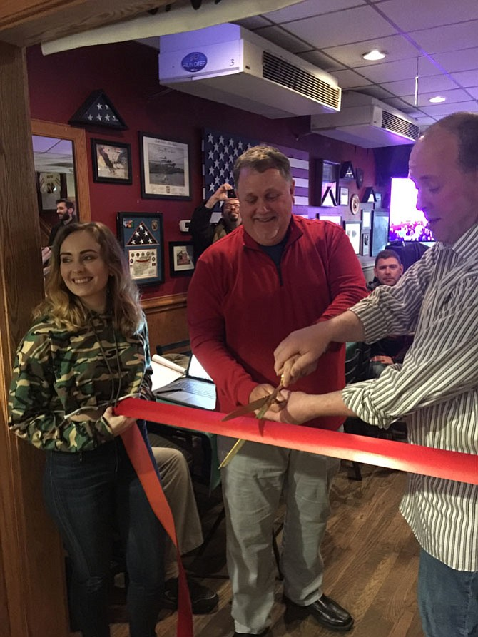 Mike O'Meara, podcast personality and the host of The Mike O'Meara Show cuts the ceremonial ribbon to the entrance of the Beer Garden, a much awaited part of Jimmy's Old Town Tavern's expansion product.