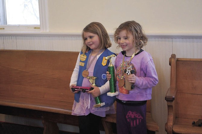The winners are two young Daisy Scouts, from left: Hannah L. and Grace M. Hannah's pinewood car raced up to 194.0 mph while Grace's car travelled at 194.5 mph.