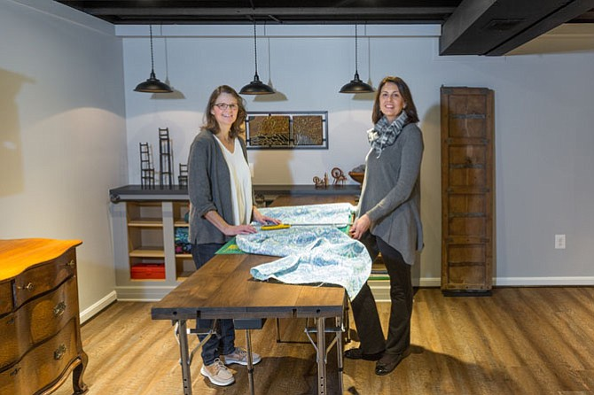 Fiber artist Shafer Dobry (left), with an assist from Dory Clemens of Foster Remodeling, demonstrates how her new custom-designed work table is used for cutting fabric. Dobry hired Clemens last year to help convert basement space into a fiber arts studio.