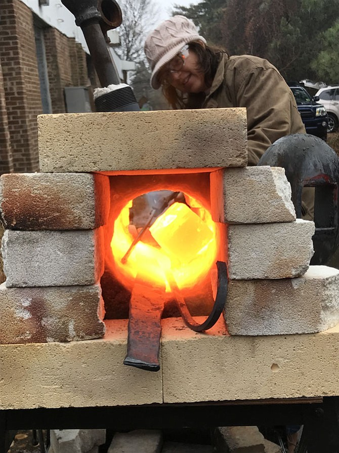 Amber Saunders heats a brick of metal at NoVa Labs in Reston until it glows a bright yellow-orange color, perfect forging heat. Saunders enjoys blacksmithing there with her son, Tyler, 16, and together they will attend Maker Faire NoVa in March.