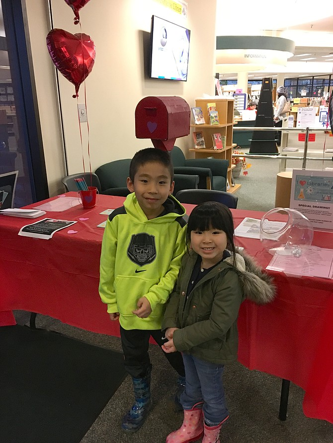Lucas Nguyen, 7, and his sister Lilymay, 4, pose by the Library Lovers Month display table at the Library Potomac on Saturday.