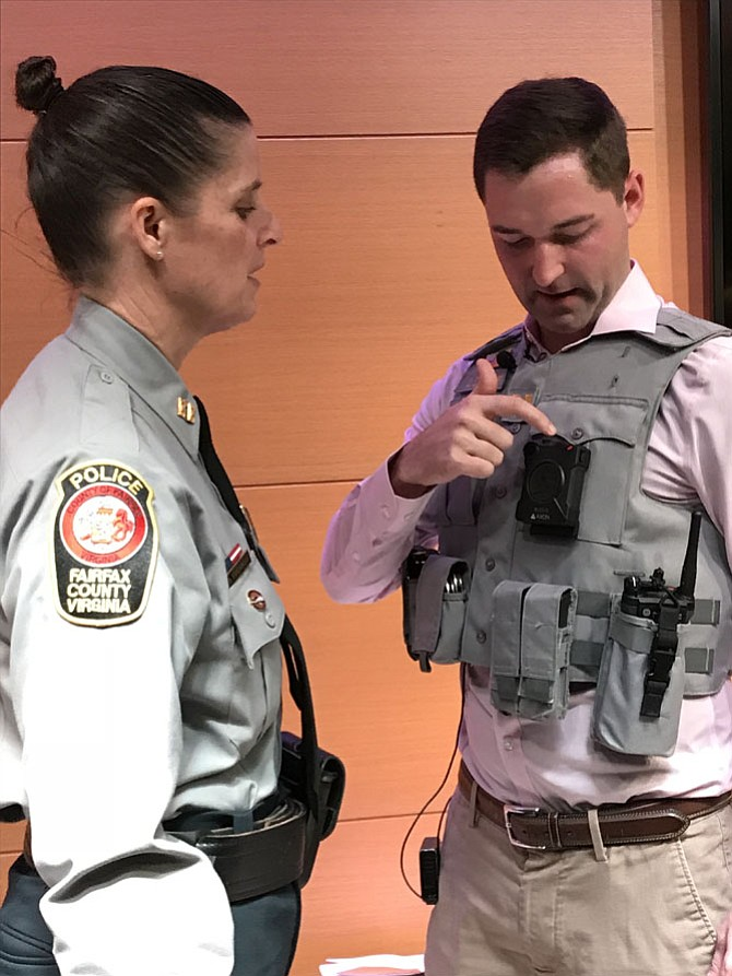 Captain Chantel Cochrane, Fairfax County Police Department, explains how the new body worn camera works as a member of the media tries one on at the Friday, Feb. 16, news conference to announce the launching of the program Monday, Feb. 19, 2019.