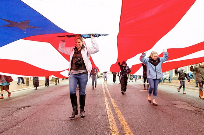 Volunteers carry the Spirit of Liberty flag through the streets of Old Town for the Feb. 19 George Washington Birthday Parade.