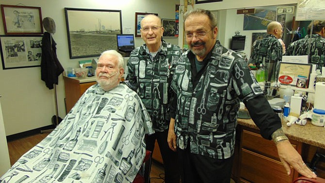 Customer Neal Nelson gets his haircut by owner Bob Stockton, with Leo Dodson (right).