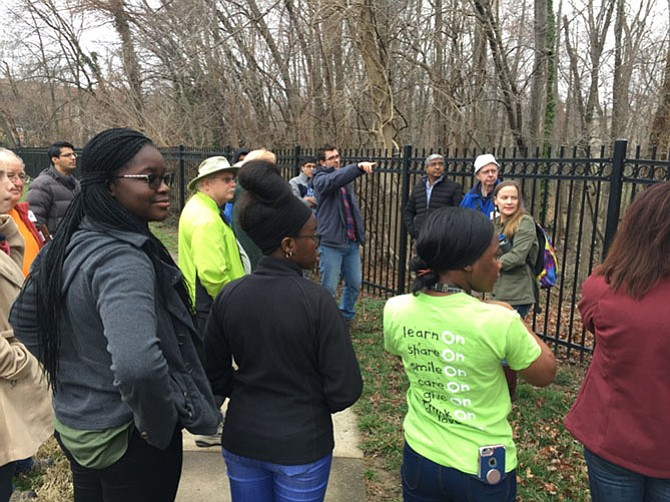 Ryan Barton, manager of community impact strategies for Community Preservation and Development Corporation, which owns Stoney Brook Apartments, surrounded by his teen volunteers shows a group of civic leaders how the creek flows through several apartment complexes.