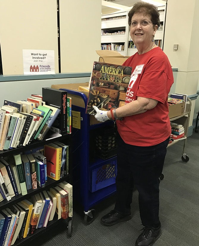 Nancy Blanton sorting books for this year's spring book sale.
