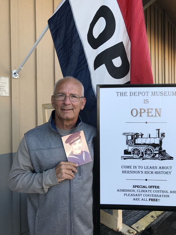David Schmelz, son of a sailor who served during World War II aboard the destroyer the USS Herndon during the Invasion on Normandy, outside the Herndon Depot Museum holding his father's U.S. Naval Training photograph. The destroyer was named after Captain Herndon, namesake of the Town of Herndon.