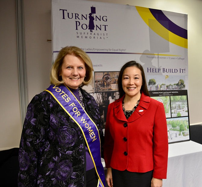 From left: Patricia Depew Wirth, executive director of the Turning Point Suffragist Memorial organization, and Herndon Town Council member and Commission for Women 2018 honoree Grace Cunningham in front of the display highlighting the designs for the national memorial planned for suffragists, to be built in the Occoquan Regional Park in Lorton.