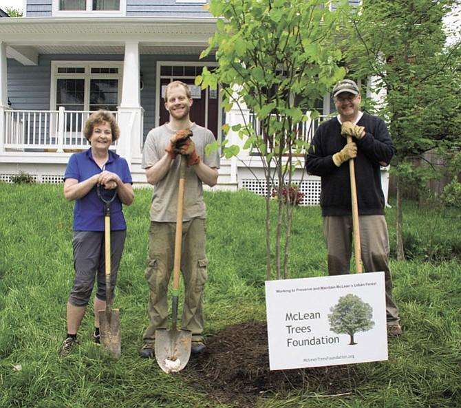 Homeowner Jason Kitson (center) plants a Redbud tree with MTF volunteers Carol Wolter and Ray Lewyckyj.