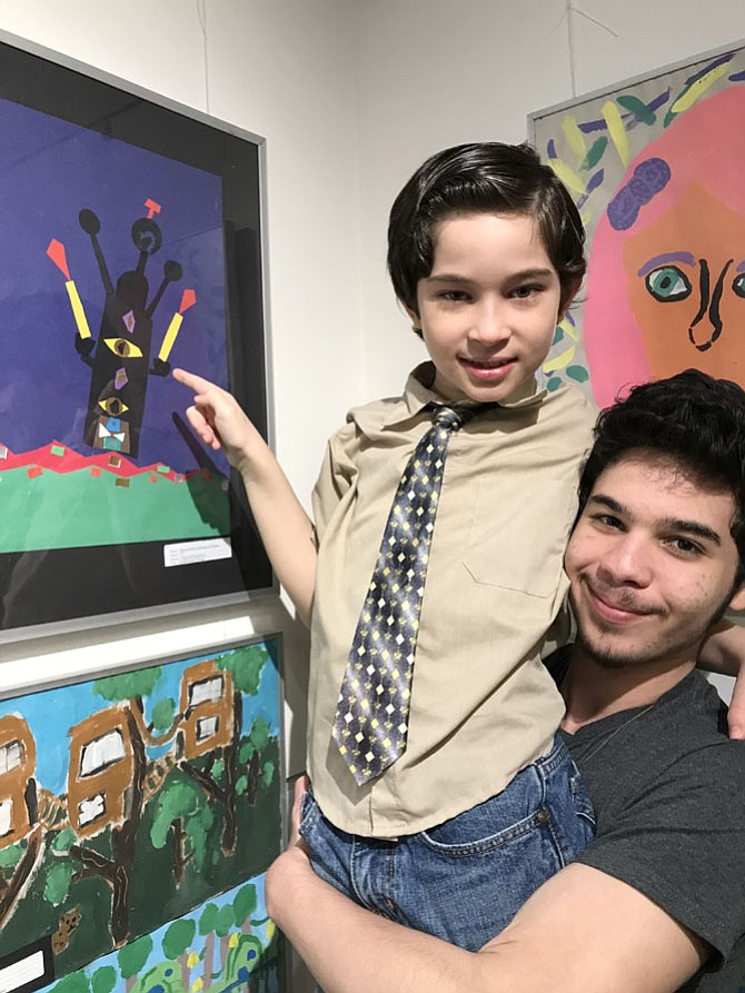 Gabriel de Moraes, 8, a second-grader at Dogwood Elementary, gets a lift up by big brother Igor so he can point out his collage selected for the exhibition at the Jo Ann Rose Gallery, Reston Community Center Lake Anne, held in celebration of National Youth Art Month.