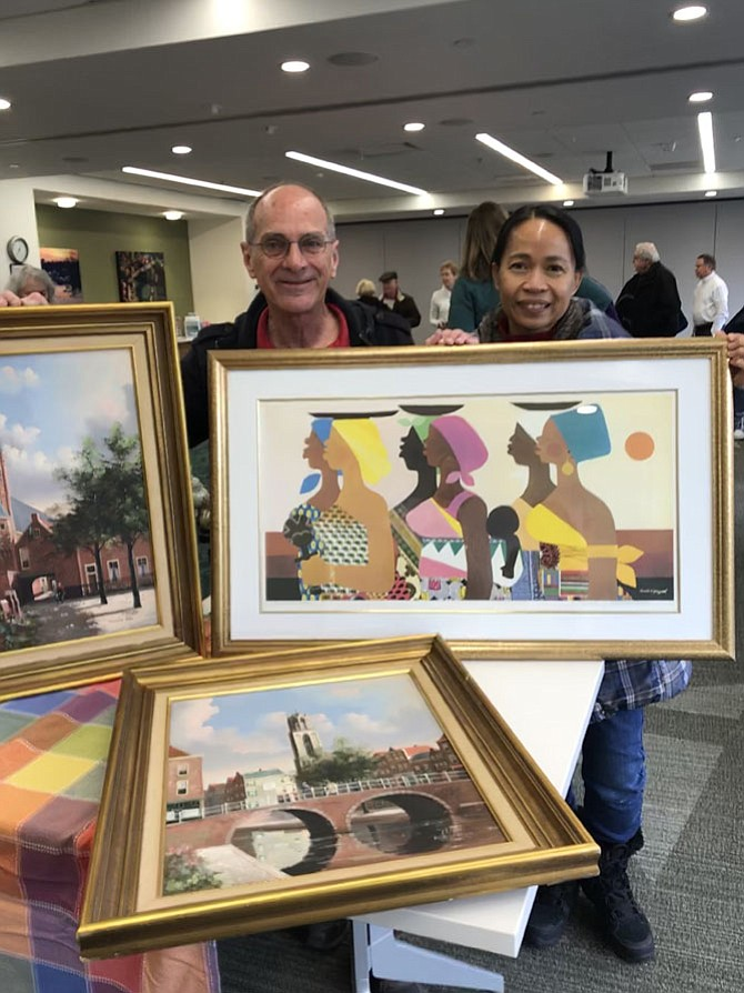 Ed and Gina Bolston, of Reston, former Herndon residents, show off the art treasures they found leaning against someone's trash can in Herndon. The works of art were identified at the Appraisal Roadshow in Reston as two original oil paintings by George Jan Dispo, a German artist and a  signed lithograph by nationally recognized American artist Varnette Honeywood (1950-2010).