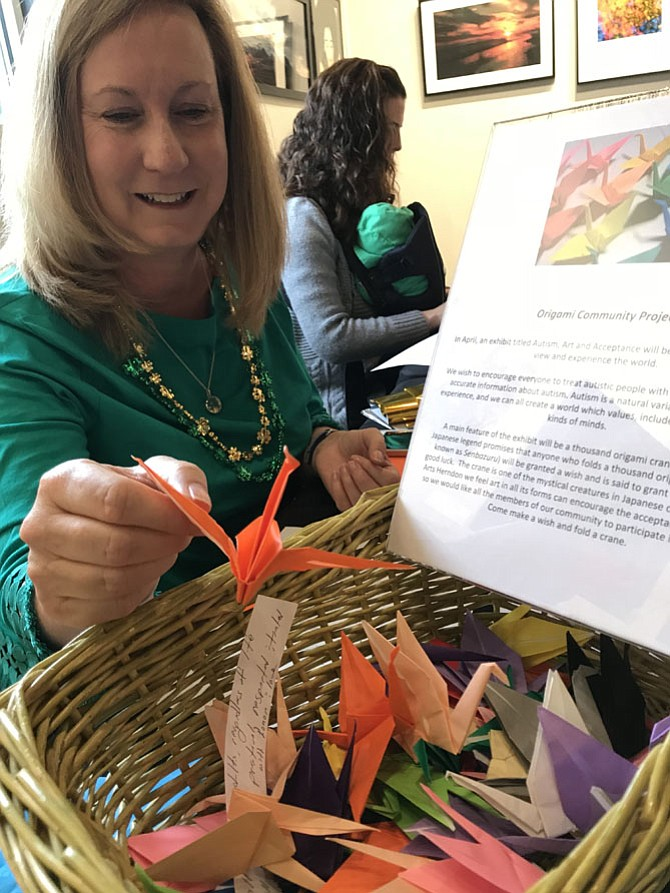 Elizabeth Vosseller drops one of her origami cranes into a box. Vosseller and her clients at Growing Kids Therapy Center in Herndon need 1,000 cranes to create a work of art in support of autism acceptance and awareness.