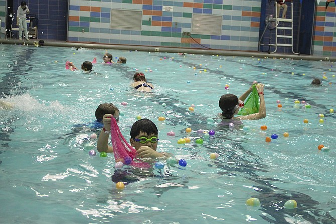 Children swim, dive and splash for eggs at the Aqua Egg Hunt produced by Herndon Parks and Recreation Department on Saturday, March 24, 2018.