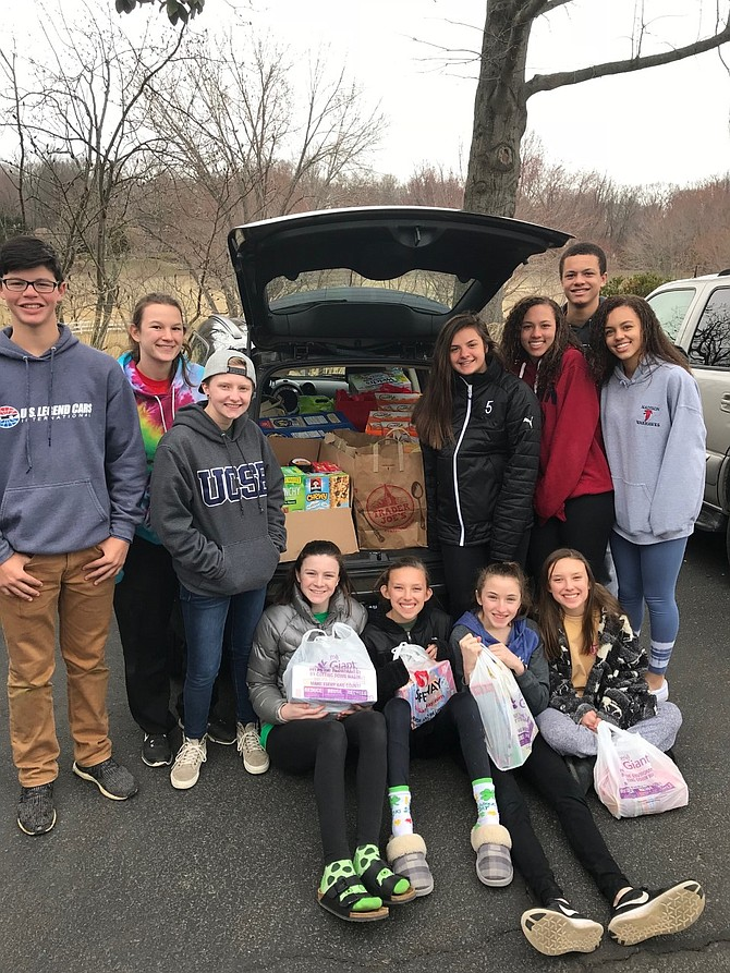 Great Falls teenagers fill the first of four cars with items collected for the Spring Break Food Drive.