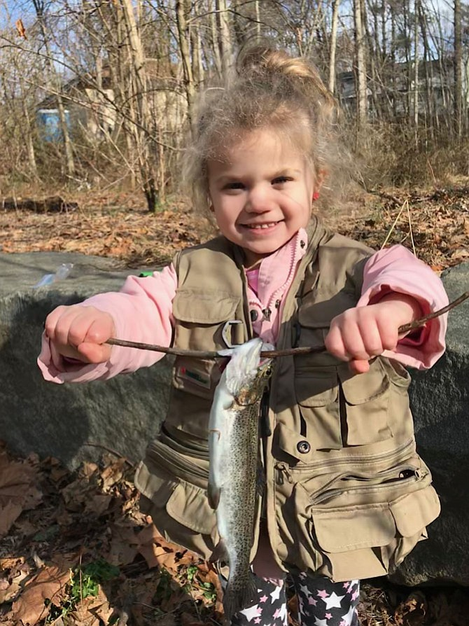 Olivia Gallihugh, 4, of Manassas, holds up one of three trout she caught in Snakeden Branch Stream during Reston Association  Annual Kids' Trout Fishing Day held Saturday, March 24, 2018.